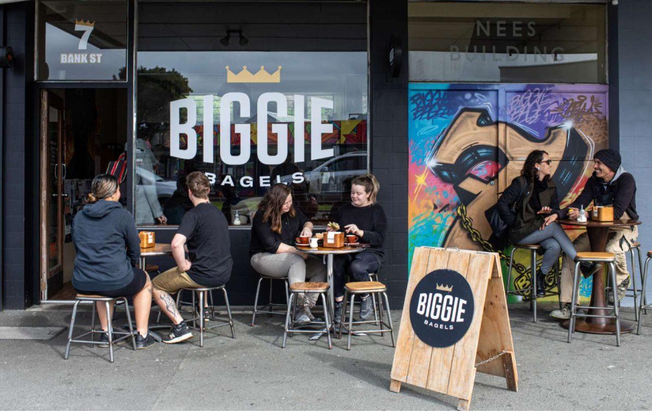 People sitting outside Biggie Bagels eating