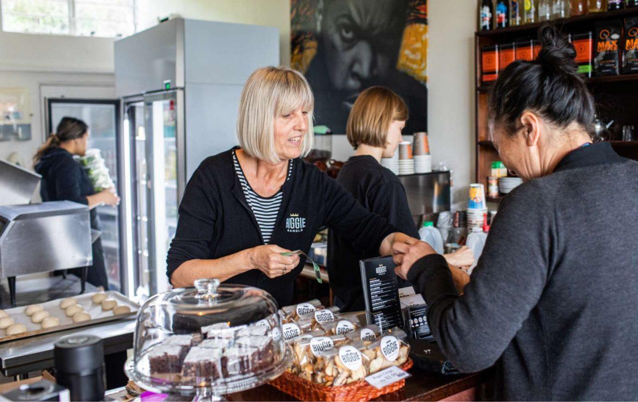 Woman serving a customer at Biggie Bagels