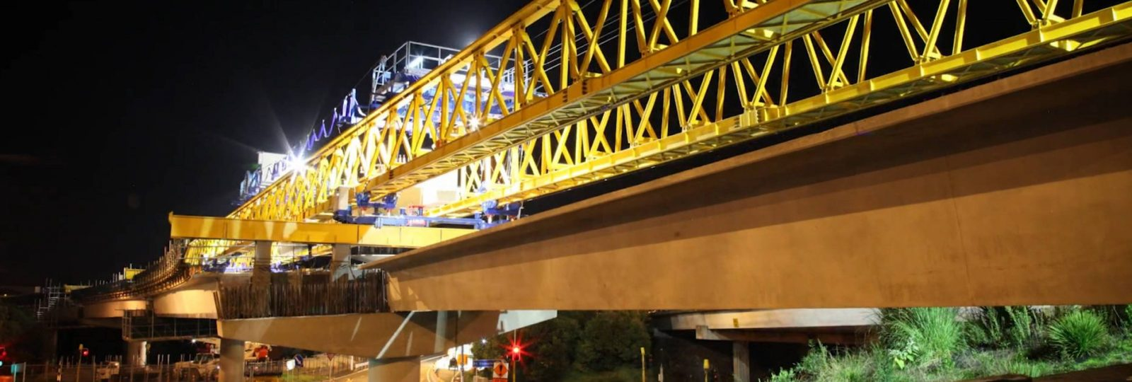 Night time shot of bridge steelwork being moved into place as part of the Waterview Connection
