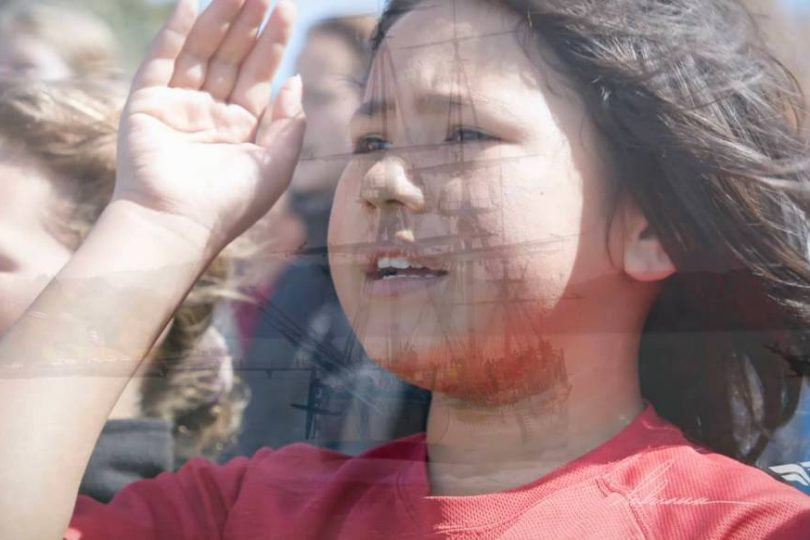 Screenshot taken from Tuia 250 video. Double exposure of young children welcoming and flotilla arriving
