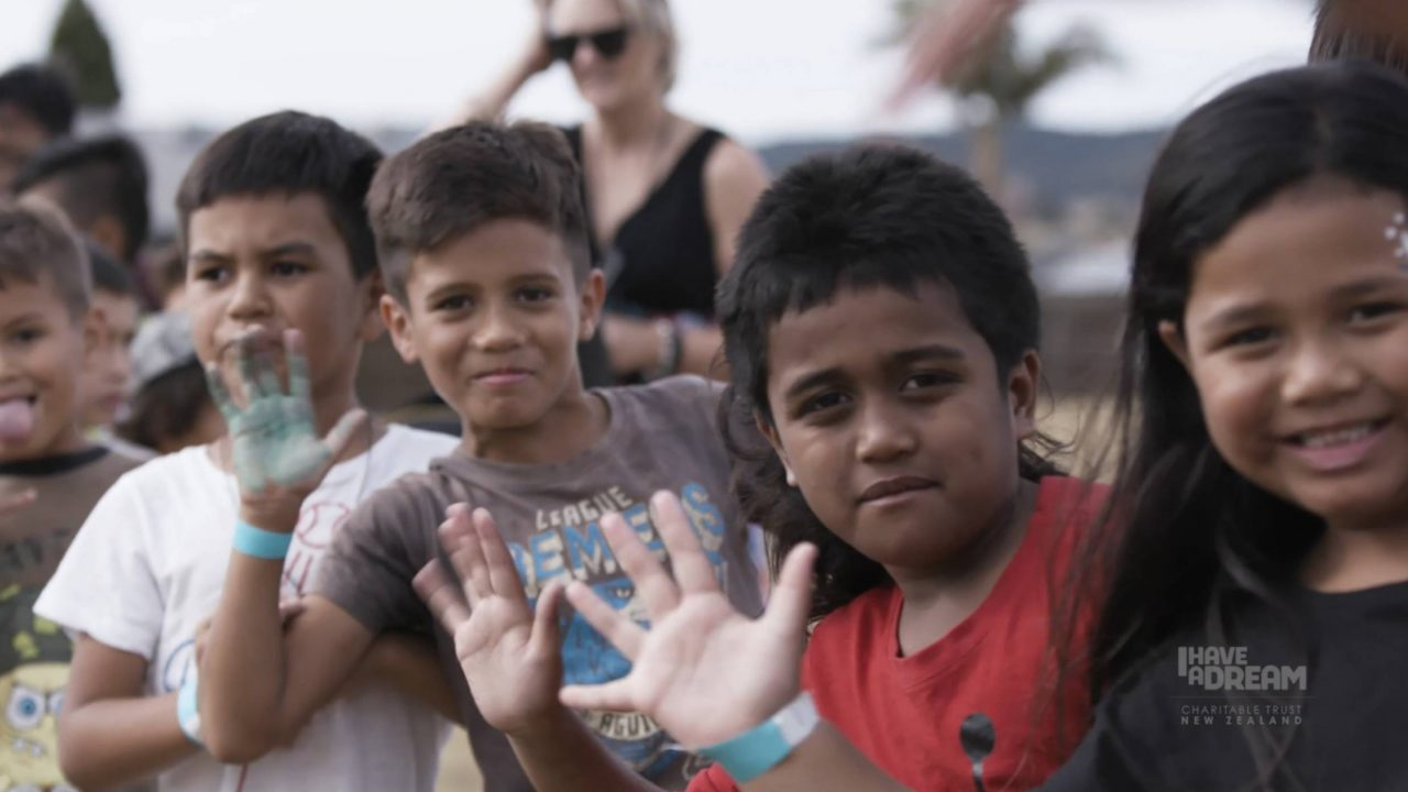 Line of young Maori children smiling and waving at the camera