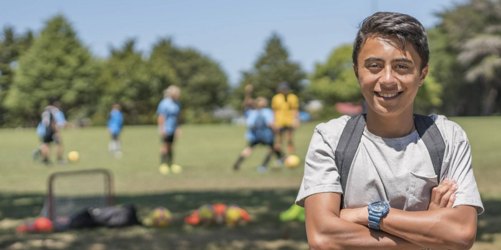 Close up of young Maori boy with people palying soccer in the background