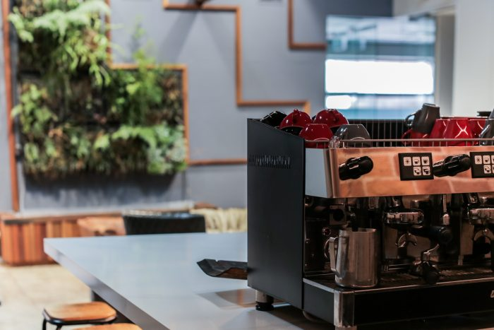 Coffee machine with living wall in the background