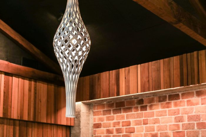 David Trubridge light fitting habging from old rustic beams and with exposed brick backdrop